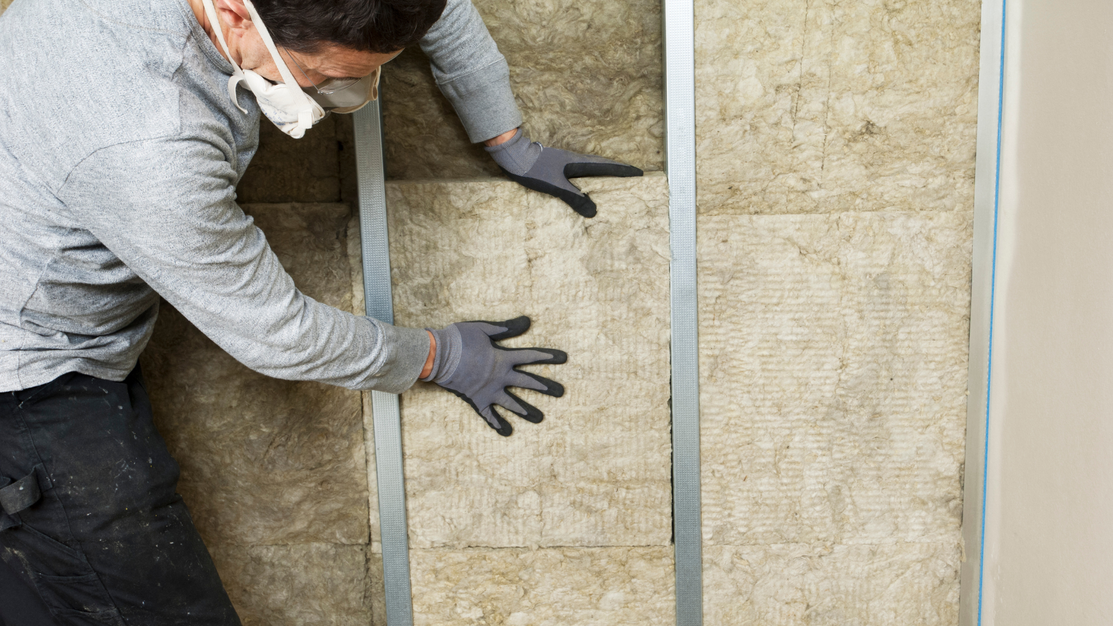 Man insulating a wall within a home.